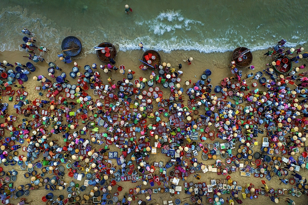 Fish market on the beach by Khanh Phan was nominated in People category.