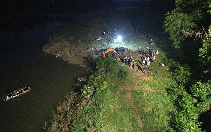 Police and other rescue forces join to retrieve a car that plunged into the Giang River in Nghe An Province, October 4, 2020. Photo by VnExpress/Nguyen Hai.