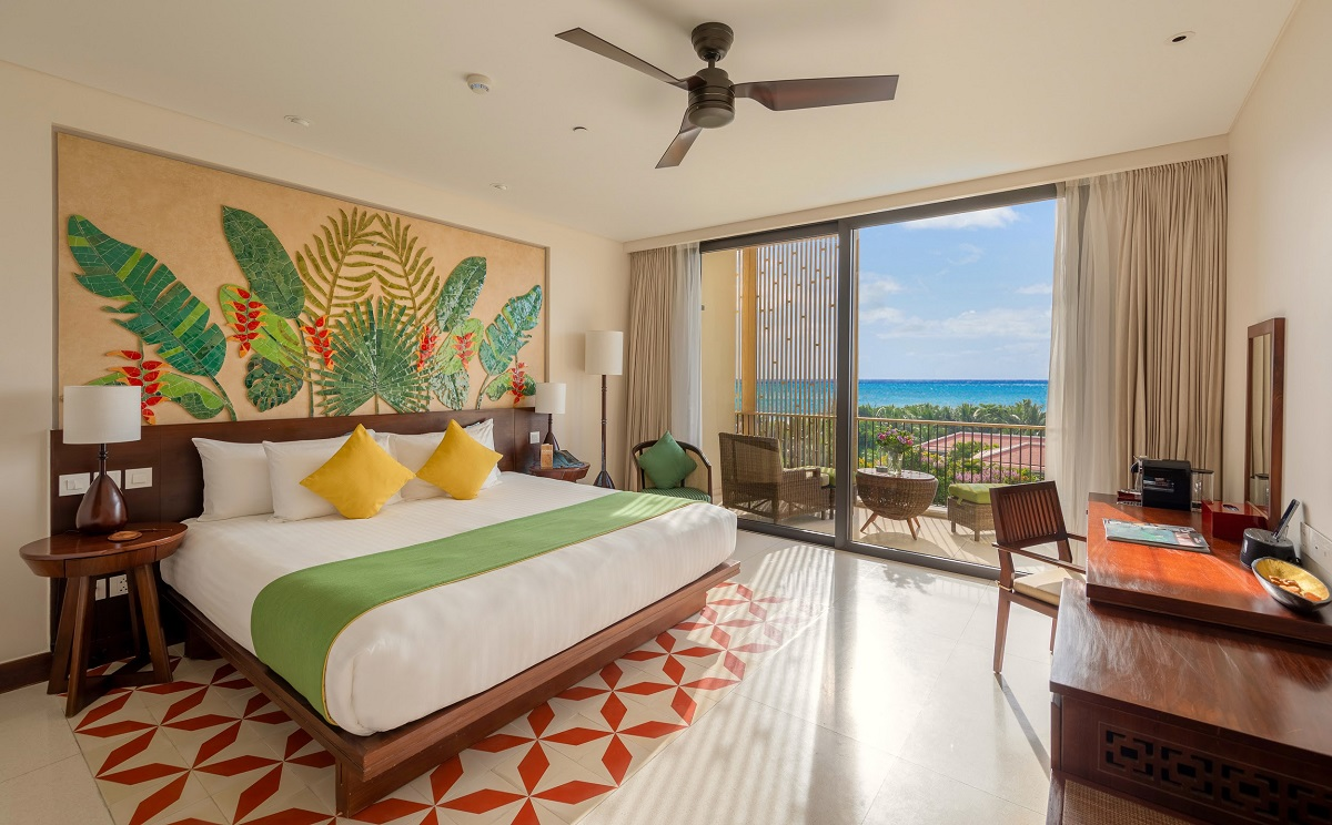 Caption: A vibrant headboard print with dark green and splashes of red from lobster claw flowers is an authentic injection of the tropical look, blurring the lines between inside and outdoors.