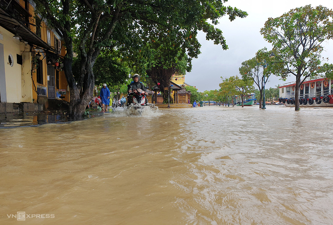 A man struggles to ride through a flooded street in Hoi An, October 8, 2020. Photo by VnExpress/Dac Thanh.