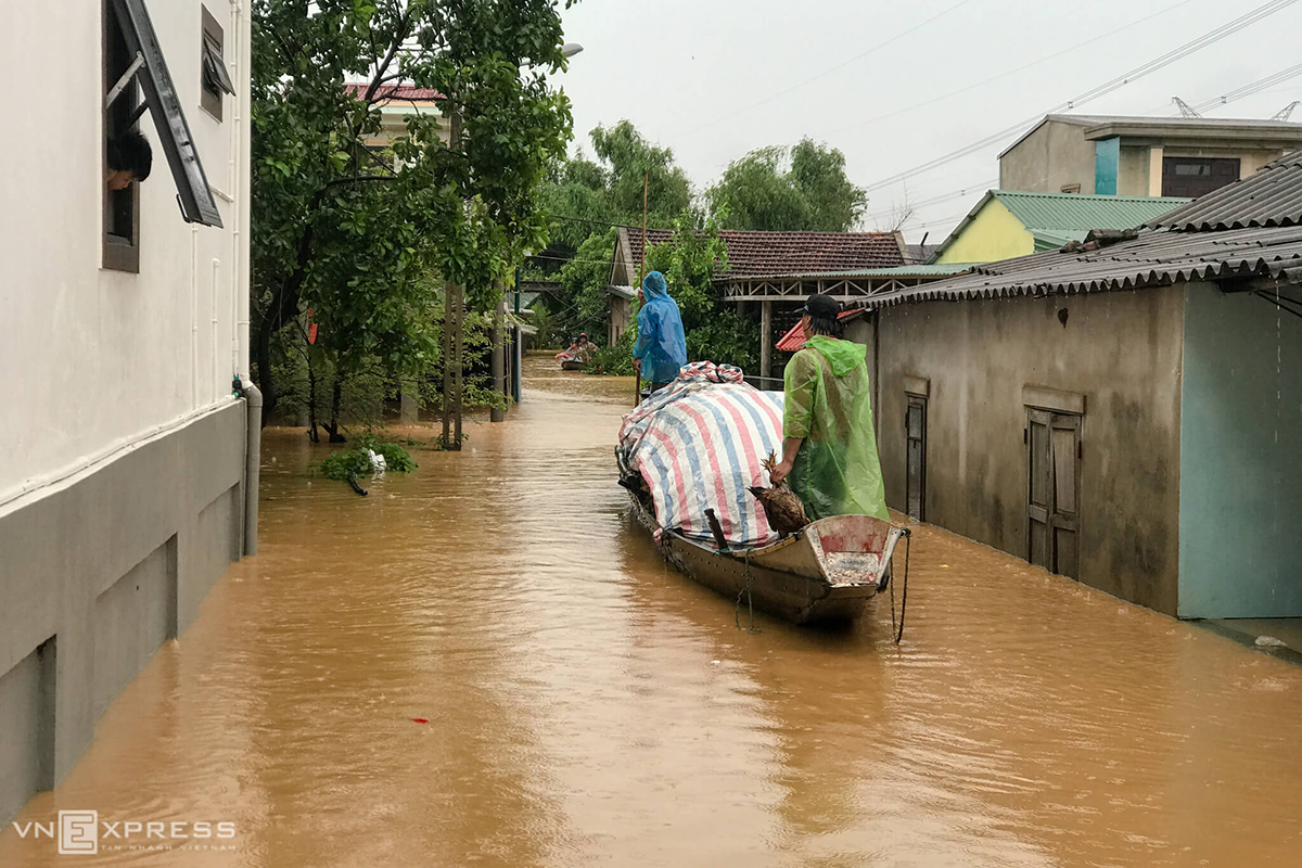 Two men use a boat to carry furniture to a dry and high place for storing in Dong Ha Town of Quang Tri. The province, along with Thua Thien-Hue and Quang Nam, has been suffering deluge caused by torrential rain that lasted from Tuesday night to Thursday morning.