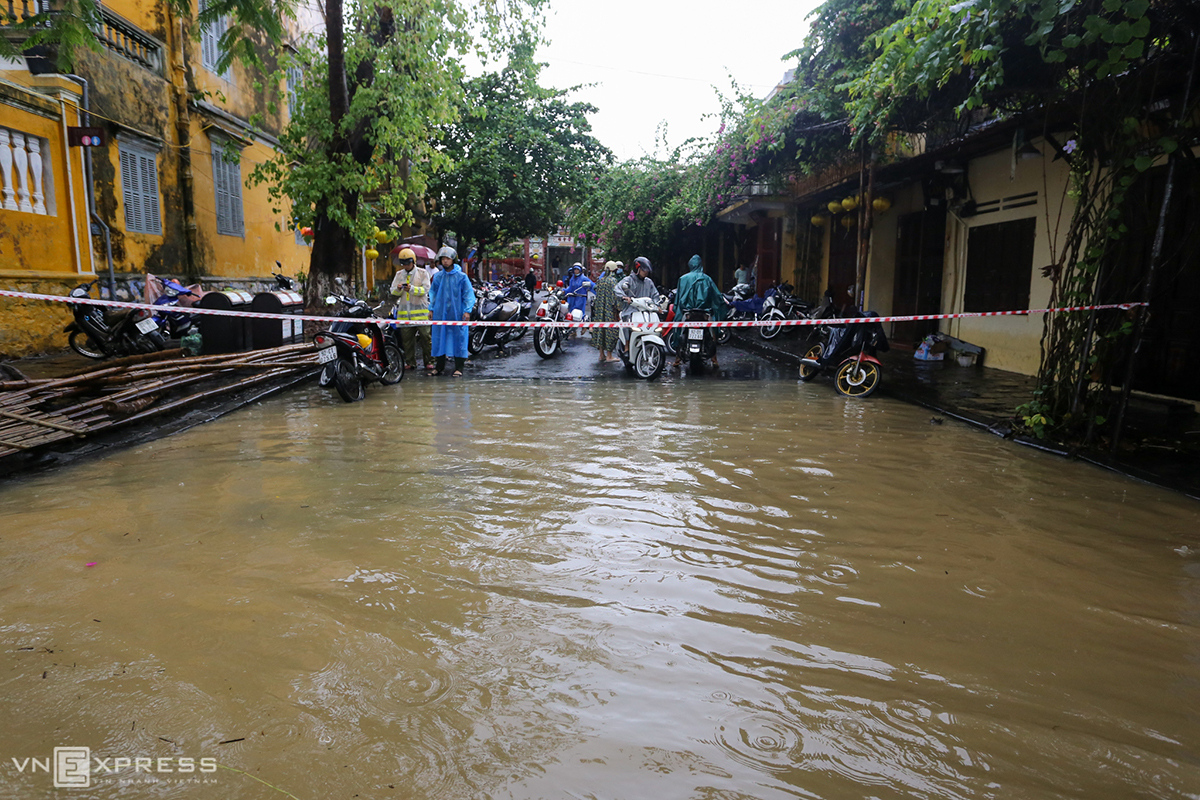 Police block a part of Chau Thuong Van Street that crosses An Hoi Bridge after flood water rises almost half a meter above the street.