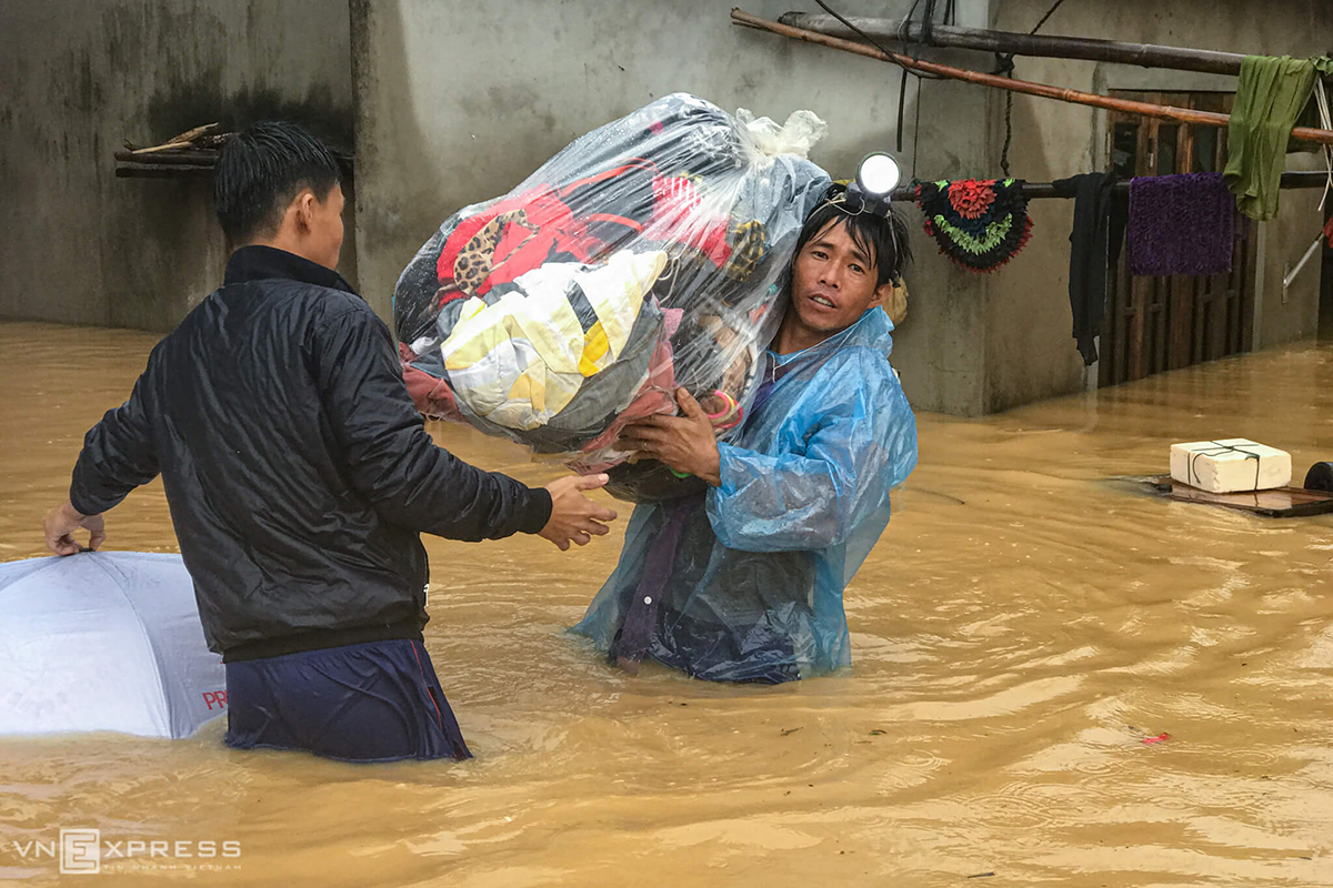 A man carries a bag of clothes to safety in Dong Ha Town. The entire central region has been battered by downpours since Tuesday as a cold spell came in contact with tropical turbulence.