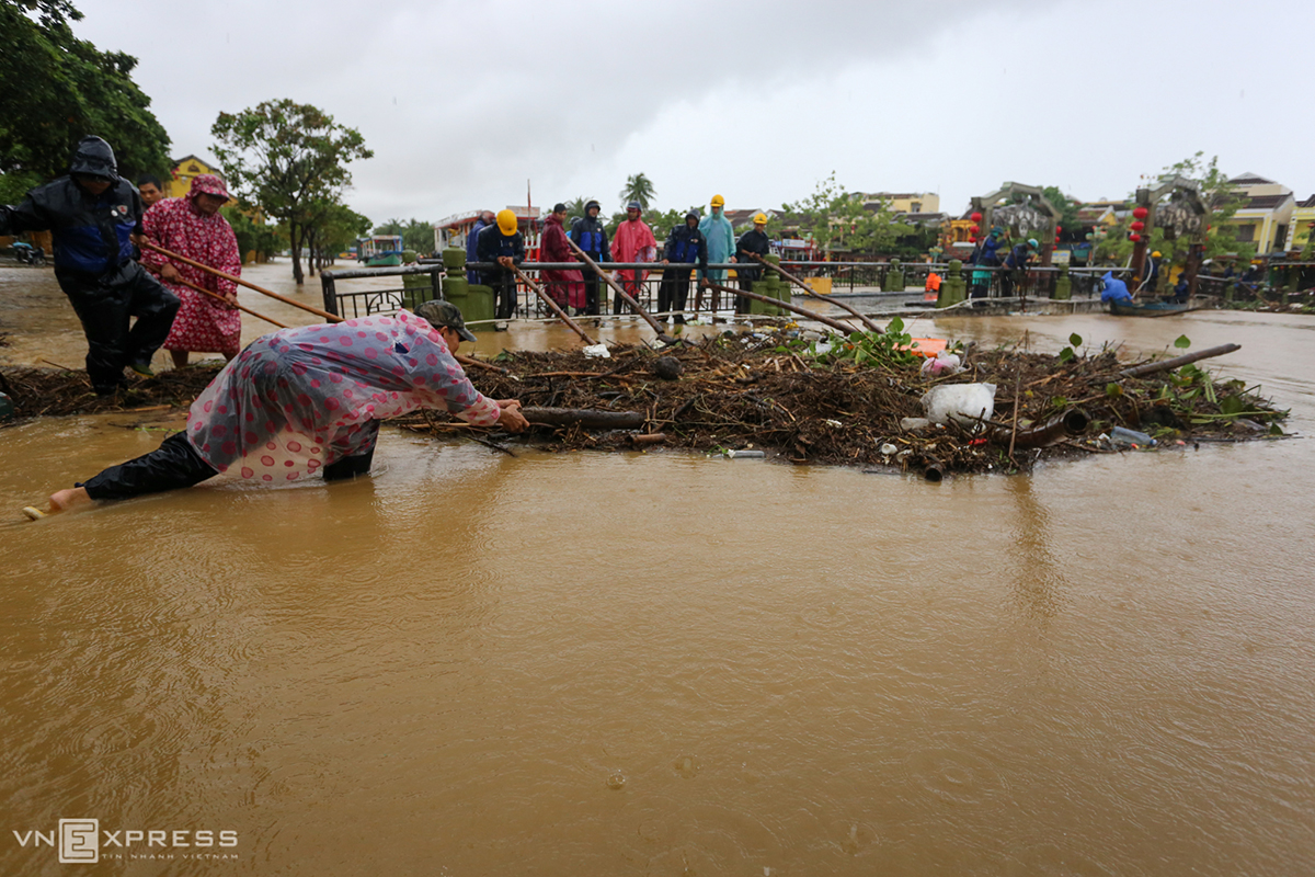 Task forces remove trash stuck at An Hoi Bridge spanning the Hoai River in Hoi An.