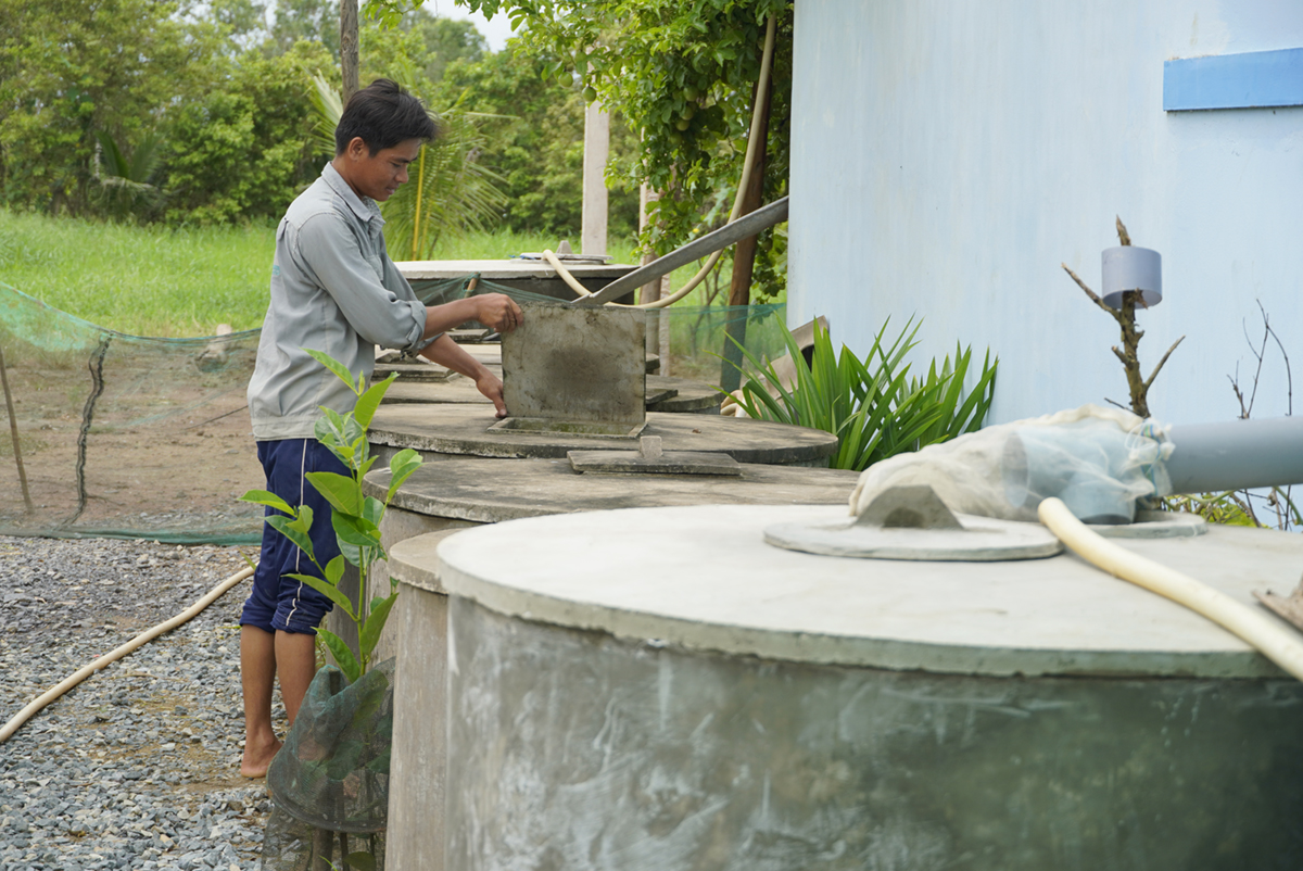 Pham Van Tien checks on 10 cement tanks that store rainwater in Ben Tre Province. Photo by VnExpress/Hoang Nam.