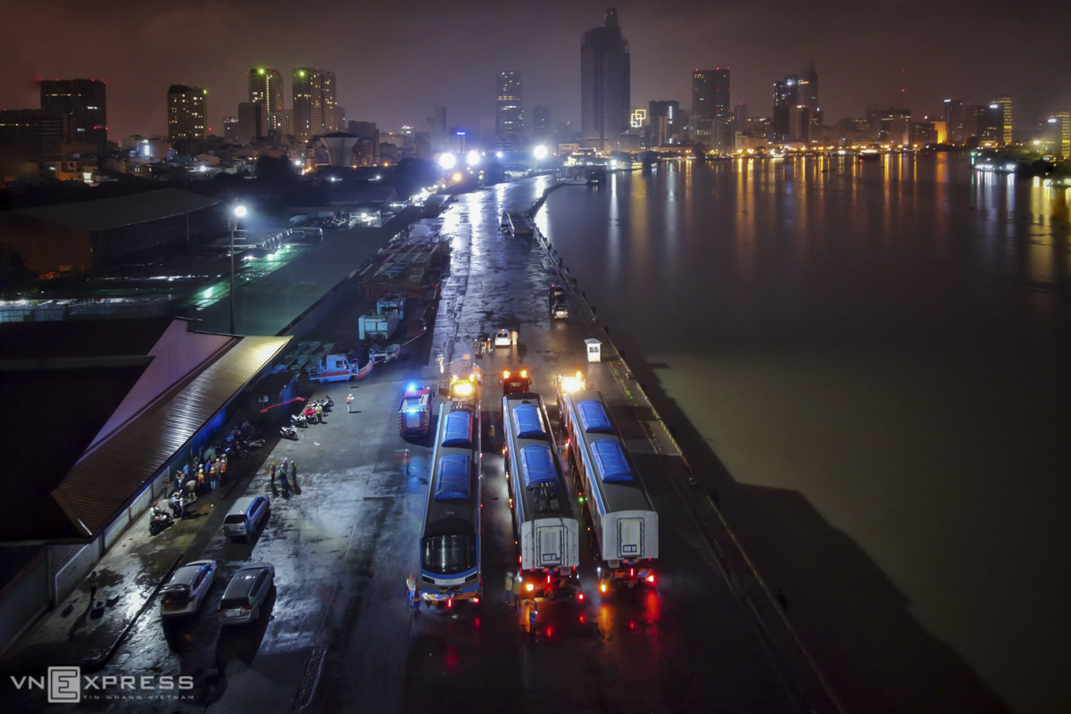 On the night of Friday, three trailer trucks are in ready position at the port of Khanh Hoi in District 4 to carry three of 51 Japanese-made coaches meant for HCMC's first metro line.The coaches arrived at the port on the morning of Thursday after being shipped from Japan. From Khanh Hoi Port, they are transported to the Long Binh Depot in District 9.