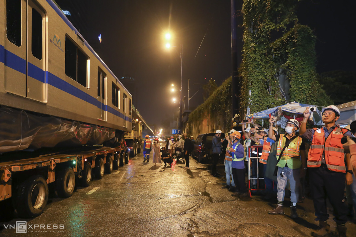 Workers that are working at the Ba Son underground station of the metro line come to watch the coaches as the trucks reached Ton Duc Thang Street in District 1.