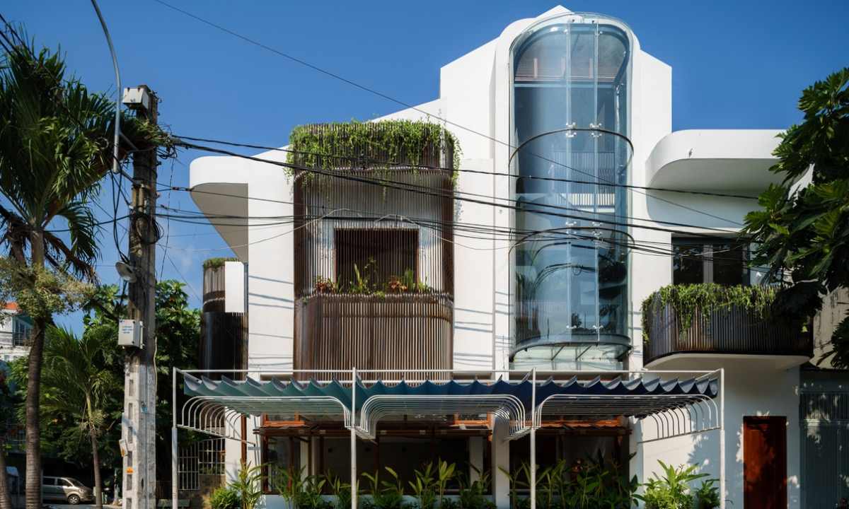 Renovating and merging two adjacent houses in Ho Chi Minh City, architects decided to embrace the sunlight by putting the staircase behind a glass wall facing the West. The curved wall made of glass makes the most of the sunset view. Photo by Dung Huynh.