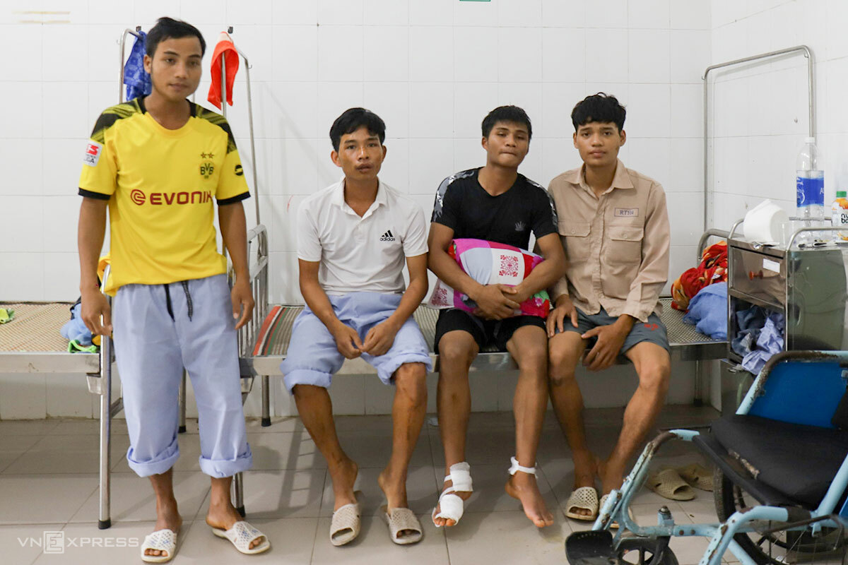 Ho Van Thoang, 27 (dressed in white) sits with three fellow workers at the Binh Dien Hospital. Photo by VnExpress/Dong Long.