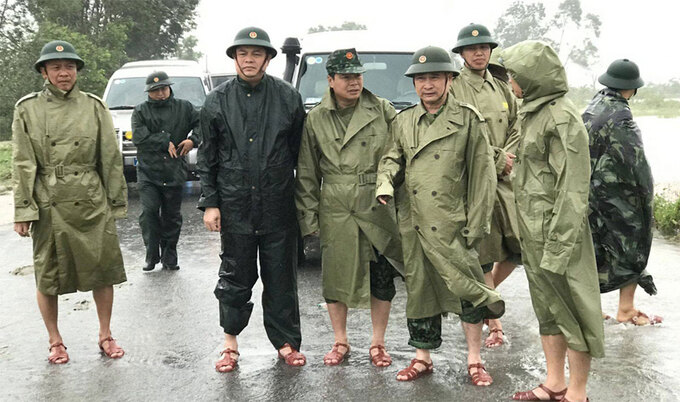 Major General Man (2nd, R) stands in the middle of the rain with his comrades while inspecting anti-flood task in Phong Dien Commune, Thua Thien-Hue Province, October 11, 2020. Photo courtesy of the 4th Military Region.