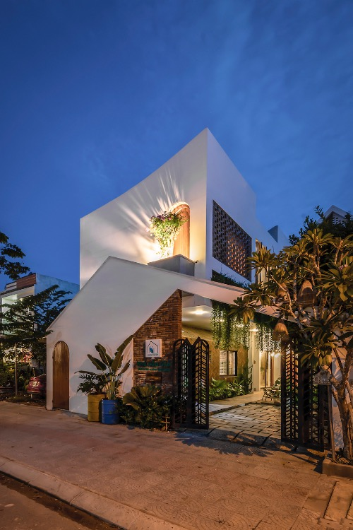 The house with a curved roof looks outstanding at night.