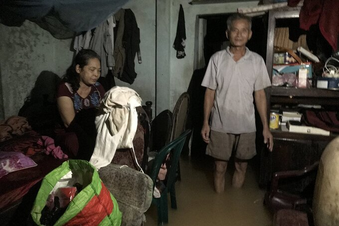 Huynh Kim Luong (R) and his wife Hoa have not left their home in Thua Thien-Hue Province for the last 10 days amid the heavy flooding. Photo by VnExpress/Hoang Tao.
