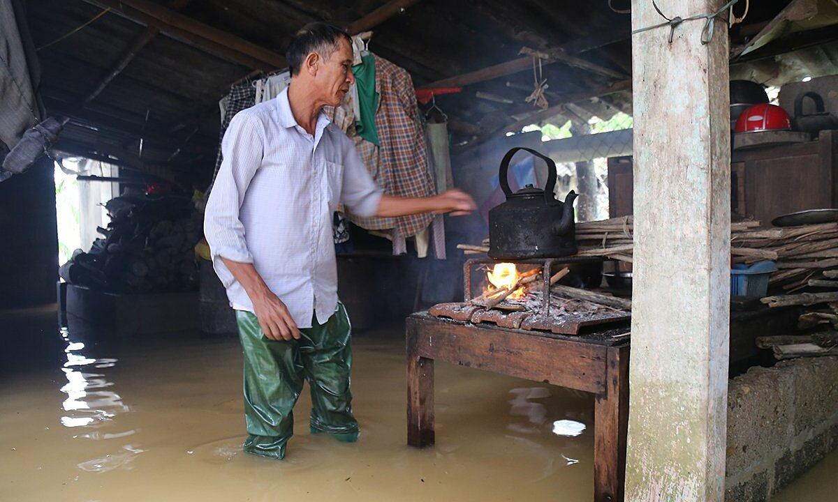 Nguyen Van Lieu wades through water to the stove in his flooded home in Thua Thien Hue Province, October 2020. Photo by VnExpress/Hoang Tao.