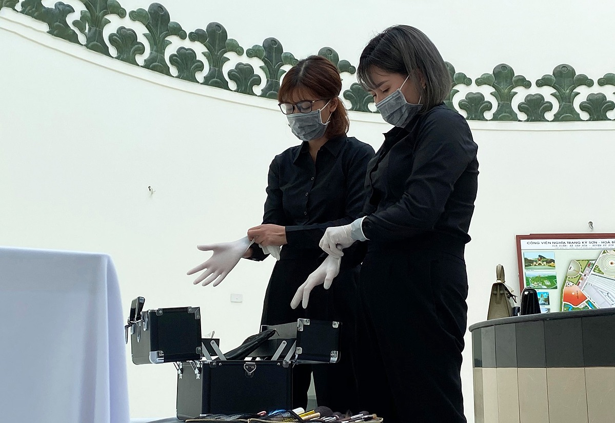 Loan (R) and an apprentice put on gloves before doing makeup for the deceased.