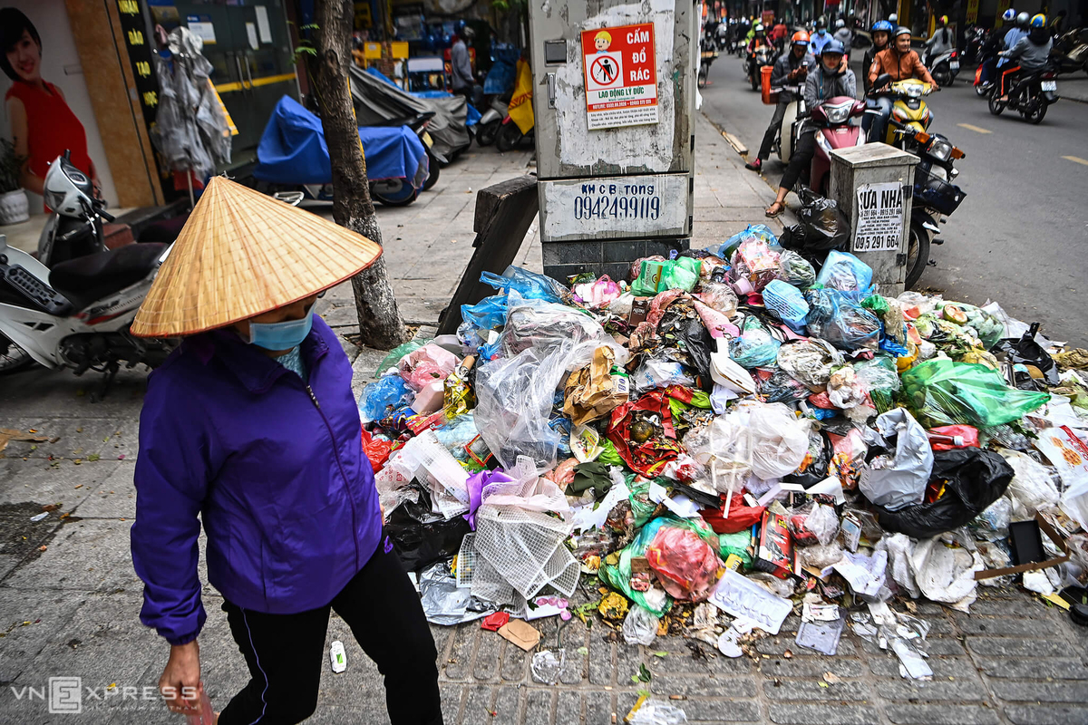 A pile of trash lies strewn along the pavement beneath a No Garbage sign on Doi Can Street. Photo by VnExpress/Giang Huy.
