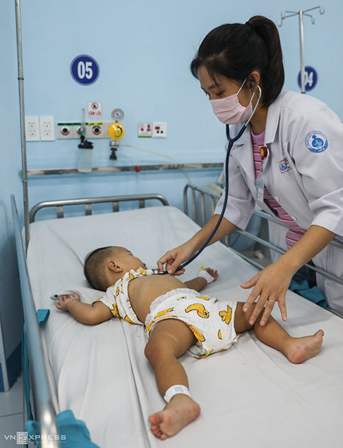 Doctor Tieu Chau Thy inspects a one-year-old boy with severe conditions. He has suffered convulsion and is now receiving intensive care in the emergency room. These days doctors and nurses sometimes cannot arrange time for lunch because there are just so many patients.
