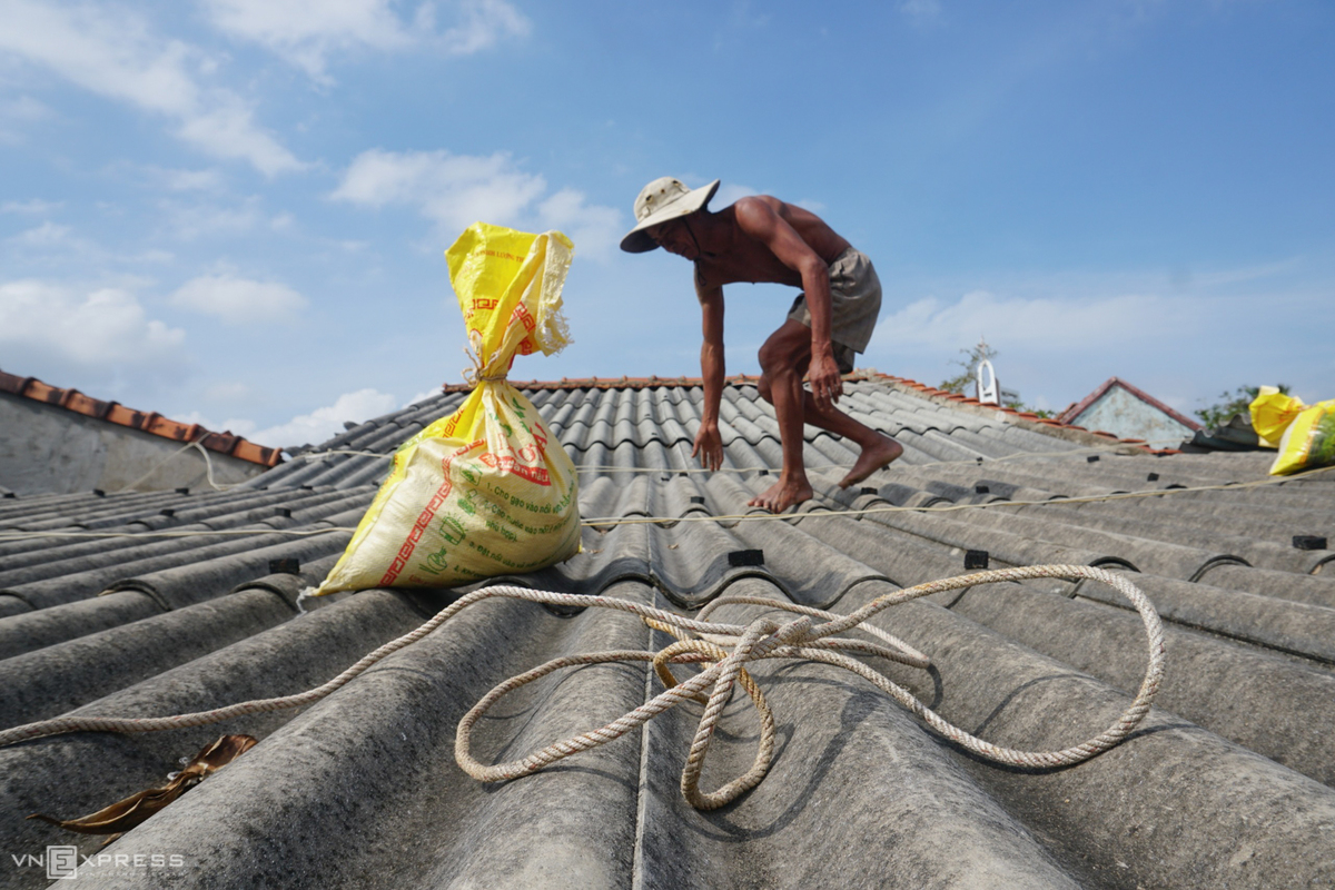 A man in Quang Ngai Province use sand bags to secure his house roof, October 27, 2020. Photo by VnExpress/Pham Linh.