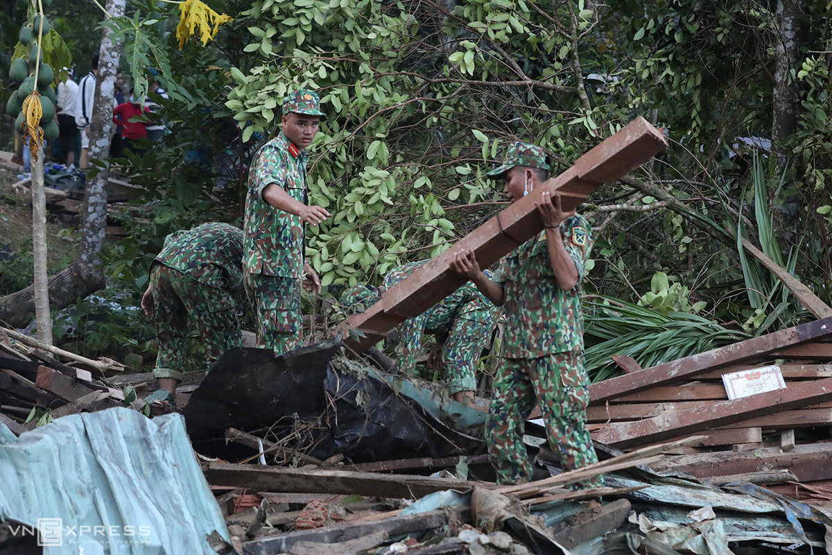Soldiers put aside what's left of the 14 houses that had been flattened by the landslide.