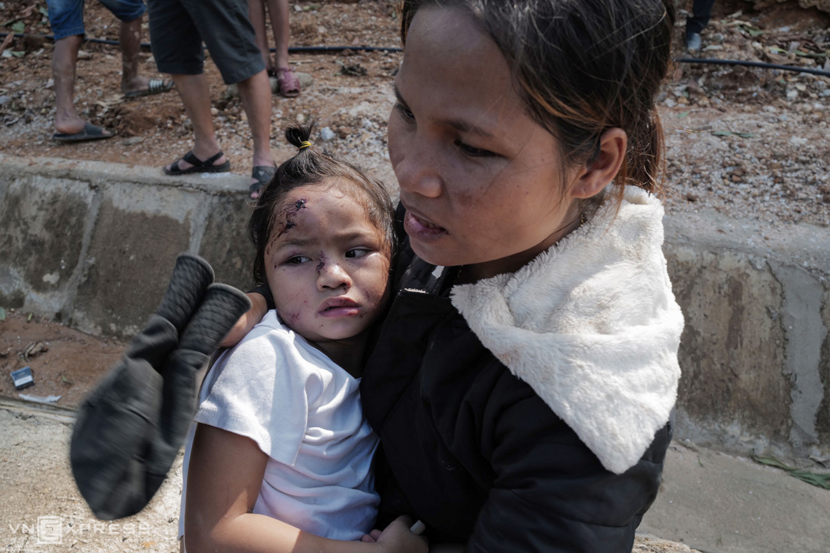 Ho Thi Ha, 28, carries her youngest daughter. She says houses in the village stands just next to high mountains.  On early Wednesday, when Storm Molave approached the central region, rains started to fall before heavy downpours and strong winds came later in the morning. Ha had already sent two daughters aged eight and five to her parents' house, which is located at a safer position than hers. Yet around 1 p.m., she heard a huge blast before seeing soil and rocks falling down like a waterfall.  Very quickly she escaped and scrambled to dig the landslide debris out. She successfully saved the two girls and her mother but failed to rescue her father.