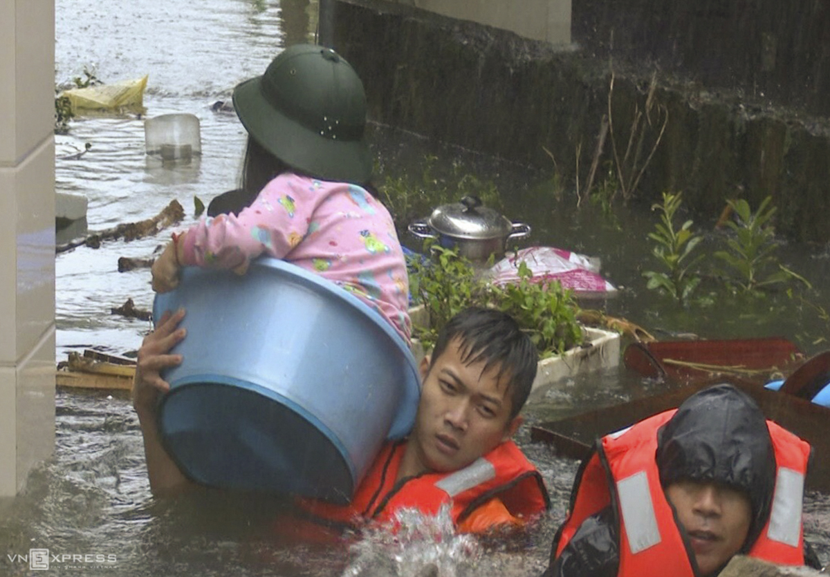 A girl is brought out of flooded residential area in Vinh Town as soldiers take residents to shelter.