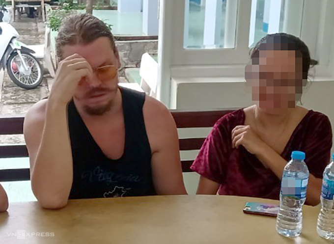 Hammett Andrew (L) pretends to faint while working with Vietnamese police October 22, 2020. Photo by Quyet Nguyen.