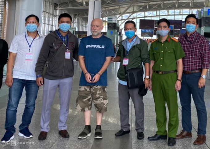 Wade Astle is eccorted by Vietnamese police to Noi Bai Airport to hand over to the U.S. police, October 23 2020. Photo by Quyet Nguyen.