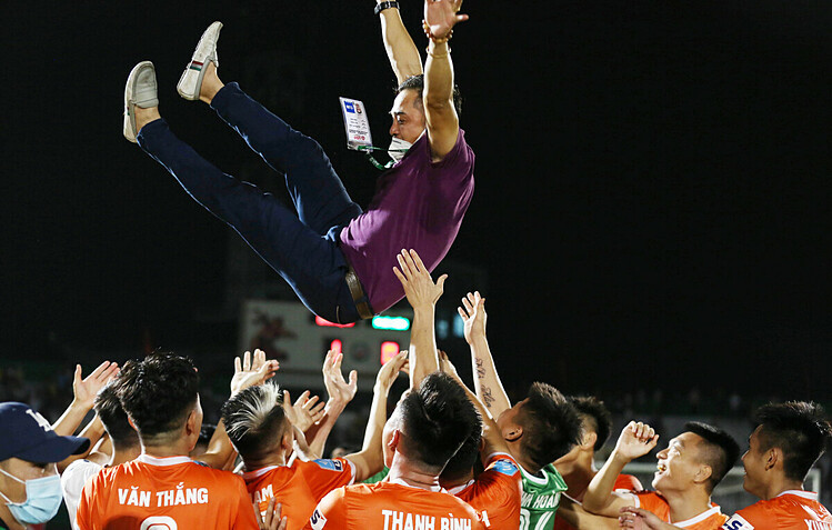 Binh Dinh FC players throw their coach Nguyen Duc Thang in the air after winning the V. League 2 title. Photo by VnExpress/Duc Dong.