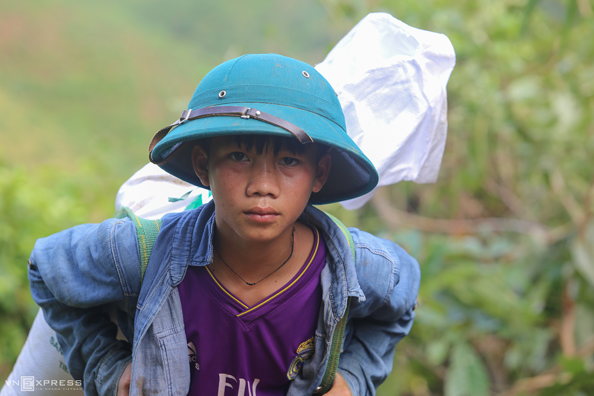 Ho Van Khanh, 14, carries 25 kg of rice on his shoulder. Khanh is the first child in a family of four. His father carried a 50 kg trip Sunday. On Monday morning Khanh followed his father to carry bags of rice homeStorm Goni is coming near and the road may erode again, so I try to carry more rice home, Khanh said.