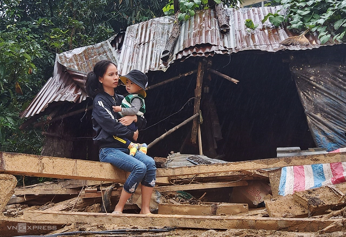 Nguyen Thi Minh Vuong holds her son as she sits on a debris left behind by a flash flood that destroyed her village on October 28, 2020. Photo by Vnexpress/Dac Thanh