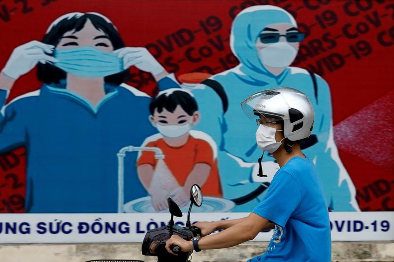 A man wears a protective mask as he drives past a banner promoting prevention against Covid-19 in Hanoi, Vietnam, July 31, 2020. Photo by Reuters/Kham.