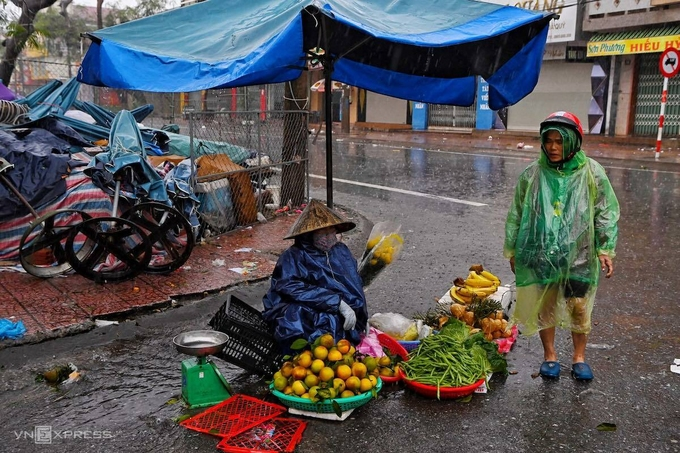 A woman in Quang Binh Province selling produces under the raining weather. Rain fell heavier as the storm hit the region at around 11 a.m.
