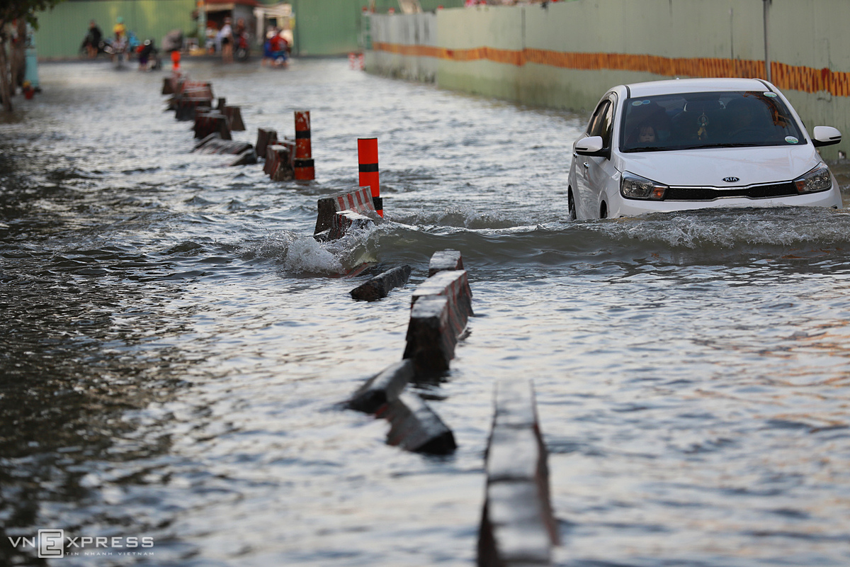 A car struggles to go through a flooded street in District 4. The center forecast the tide to reach 1.76 meters at the Nha Be Station at 5 p.m. on Monday, the highest levels this year.