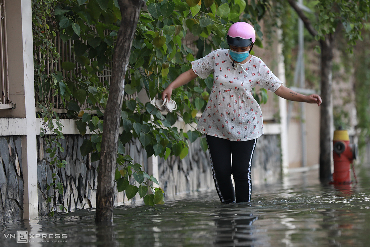 Truong Thi Nhu Loi, 19, from Dong Nai, which neighbors HCMC, walks through a flooded street to reach her relatives house in District 4 after her motobikes engine died. The street was flooded and my husband had to walk with our motorbike ahead, I was pregnant, so I must carefully follow the sidewalk, Nhu said.