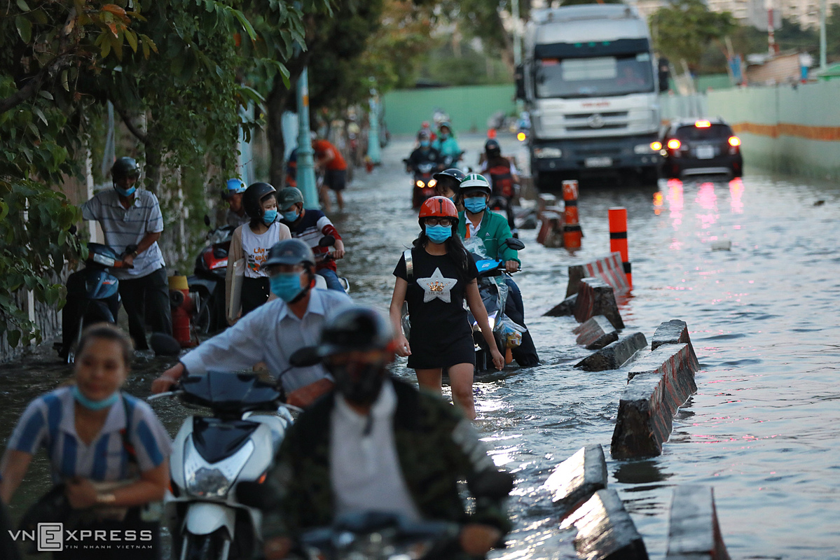 At 5:30 p.m. when the water level receded motorbike drivers walked with their motorbike through a street submerged under 30 cm of water.