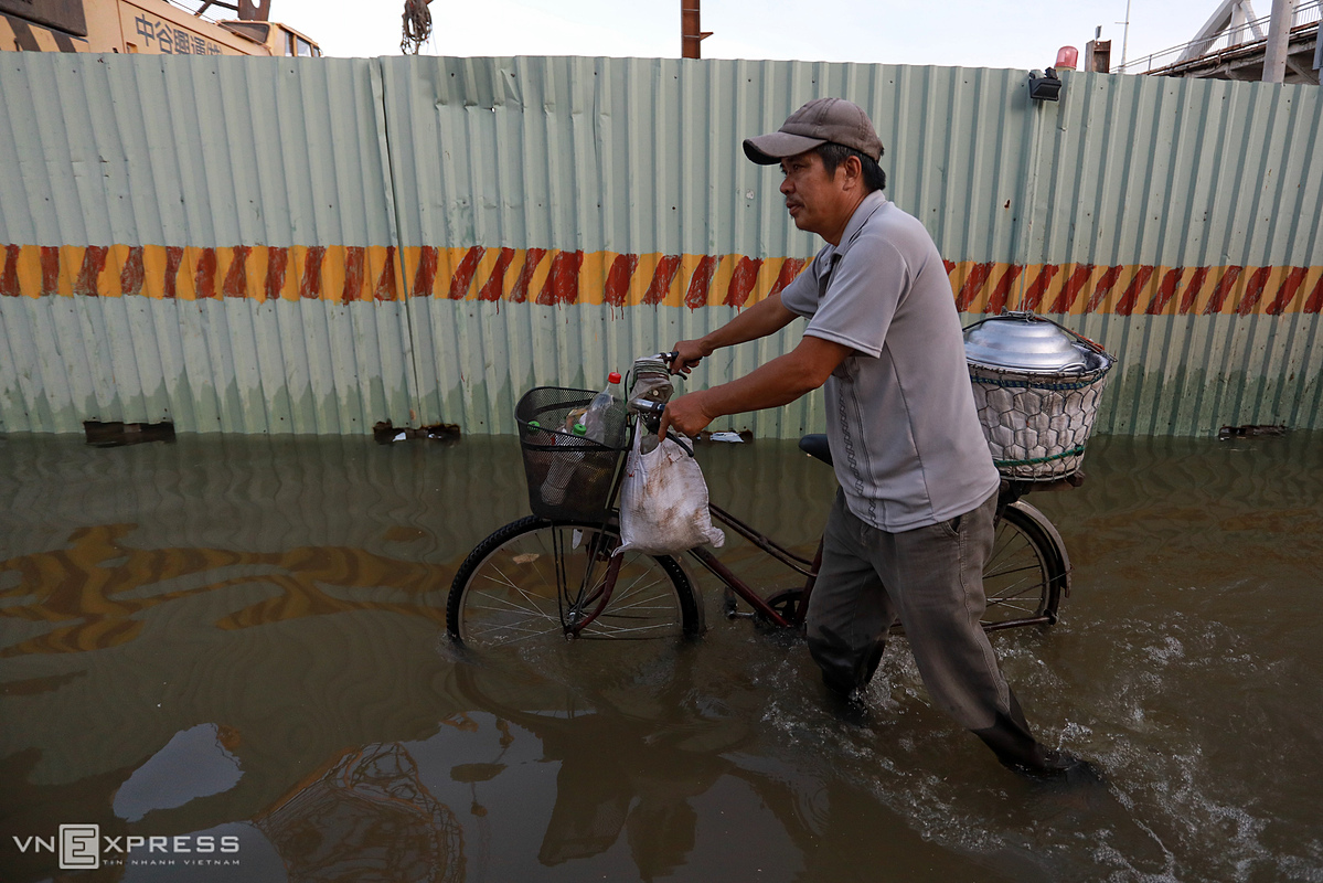 Roads were so difficult to travel. If not be careful, it would be easy to get stuck in potholes, said Huynh Minh Thong, who walked with his bike selling banh gio (pyramidal rice dumpling).