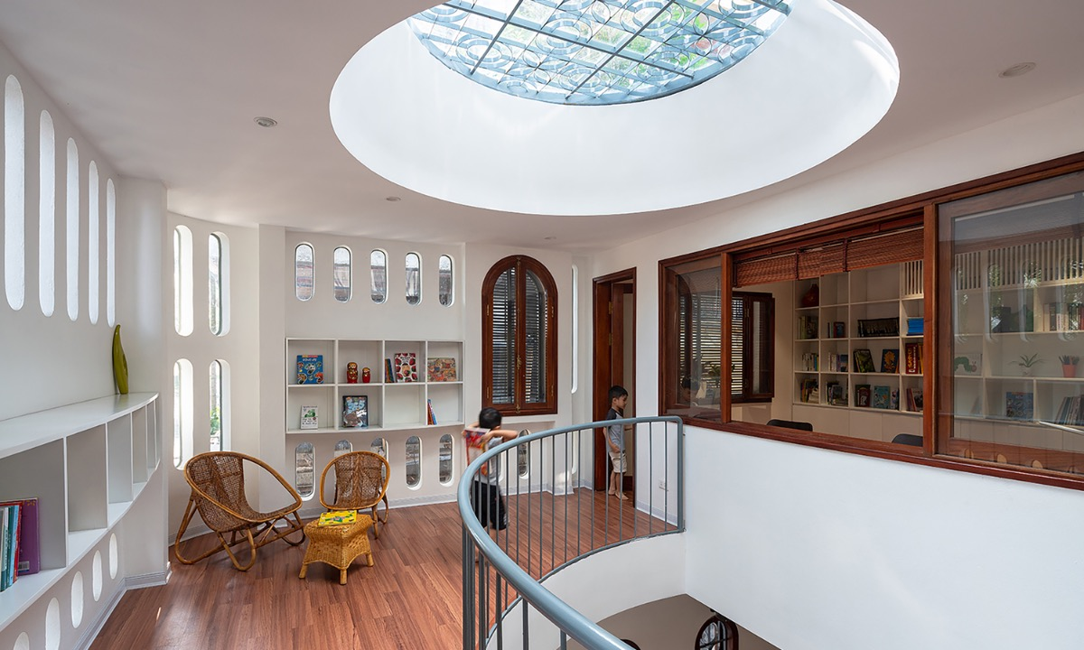 The house has three floors, and the common space is placed on the second one. A void on the second floor with a circle on the top boosts air ventilation and makes the house filled with natural light.