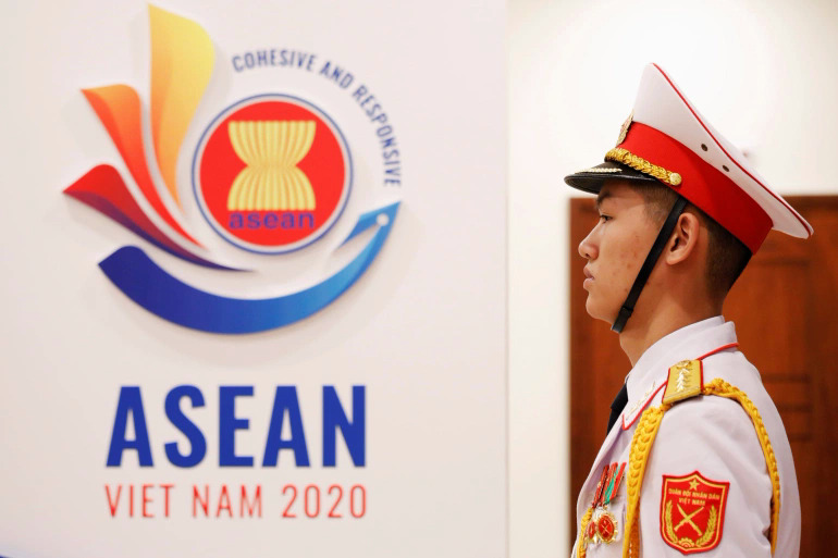 A honor guard stands near the logo of ASEAN 2020 in Hanoi. Photo by Reuters/Kham.