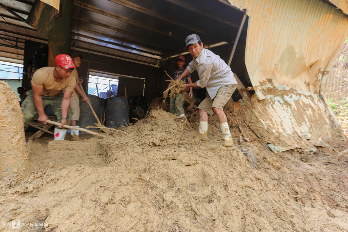 A company has staff clean up its warehouse, which has been covered by a layer of mud that is almost half a meter thick.