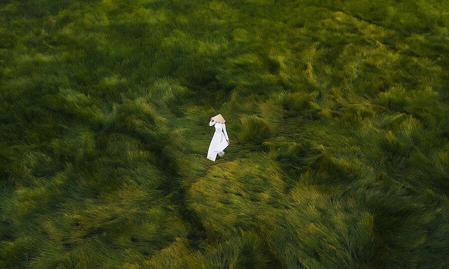 A woman wearing an ao dai and walking on a paddy field of central Quang Ngai Province is captured by photographer Duy Sinh. According to Sinh, In my photo, portraits with ao dai are usually only taken with a terrestrial camera, but using a drone for this photo showed a different, broader, and wider view with the scenery of the vast meadows.