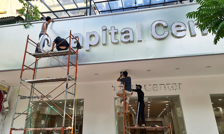 Workers are apparently changing the stores name from Apple Center to Capital Center. Photo by VnExpress/Luu Quy.