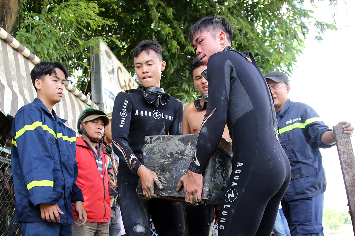 Divers of the PC07 units carry a safe box at the Dia Canal in Nha Be District. Photo by VnExpress/Dinh Van