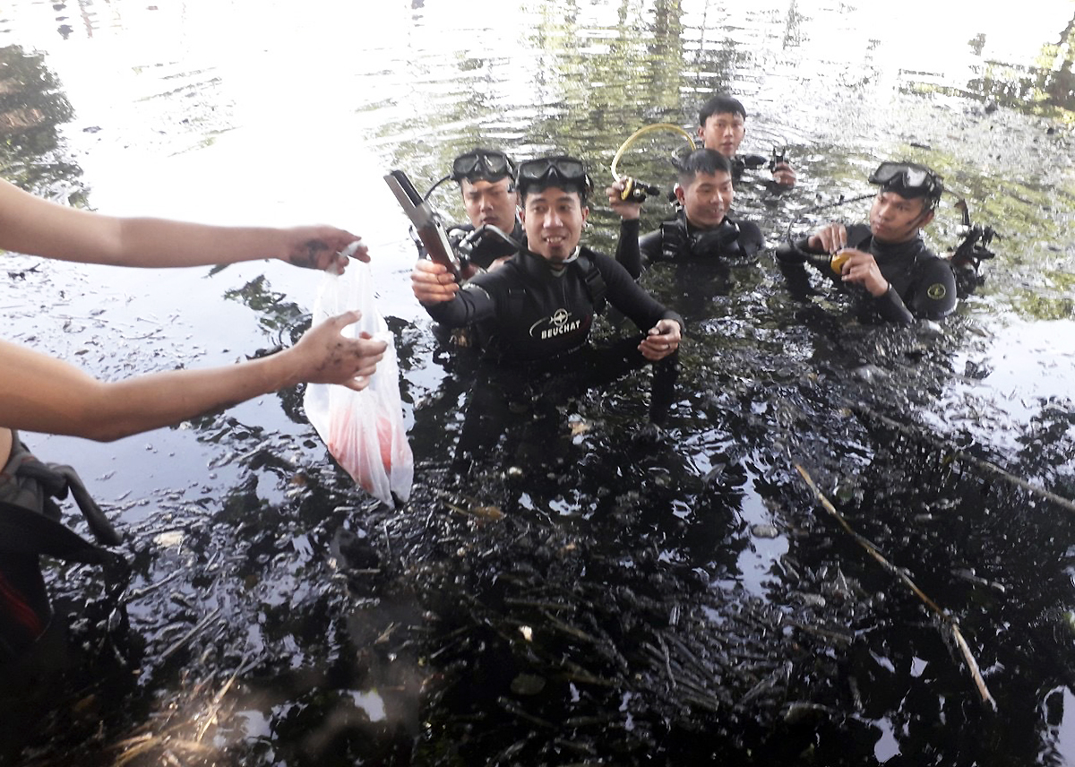 Nguyen Nhat Phong hands over parts of the shotgun he and his team find in the bed of the Lang Le Canal in HCMCs Distrcit 12, 2019. Photo by the HCMC Fire Prevention and Fighting and Rescue Police Division.