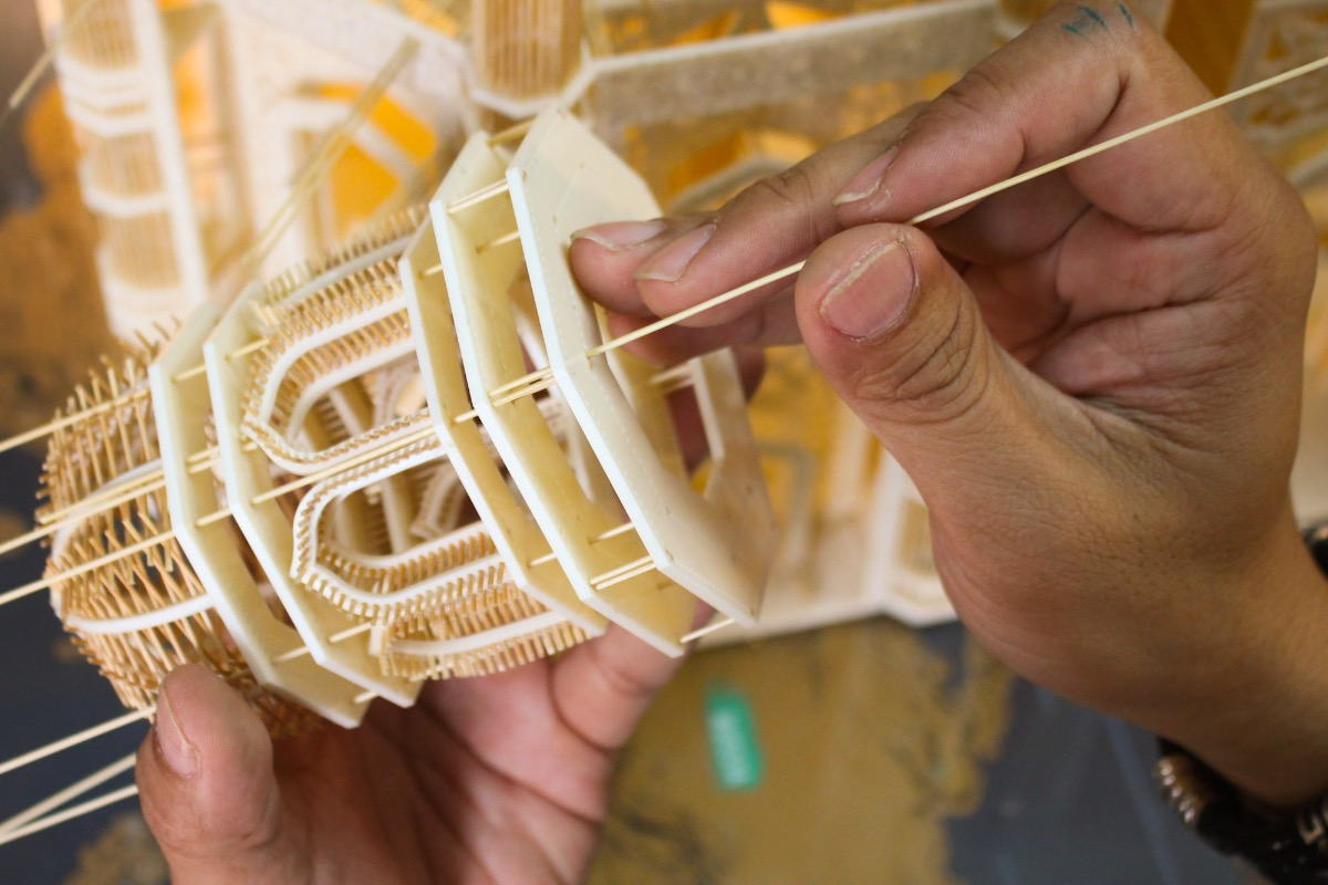 Laser-cut mica pieces, 2-mm thick, are connected by toothpicks and glue. These pieces are the base for the 'buildings.'