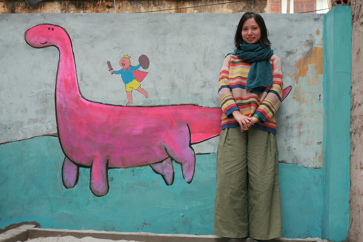 Chu Kim Duc stands by a painted wall at a Think Playgrounds project in 2015. Photo courtesy of Think Playgrounds.