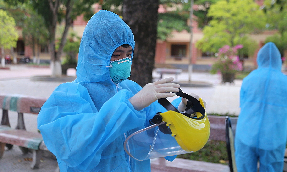 A medical worker prepares to wear a face screen before handling Covid-19 test samples in Quang Tri Province, central Vietnam, August 5, 2020. Photo by VnExpress/Hoang Tao.
