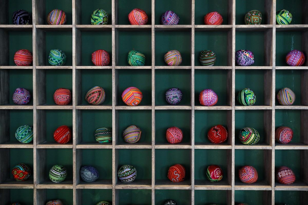 Decorative globes made in ethnic patterns decorate a shelf.