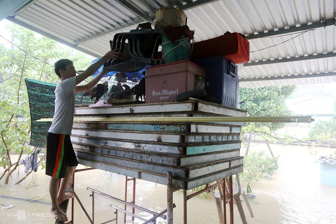 Nguyen Trung Quang in Nha Trang puts his furniture on to a scaffolding when the floodwaters overflow his house, November 30, 2020. Photo by VnExpress/Xuan Ngoc.