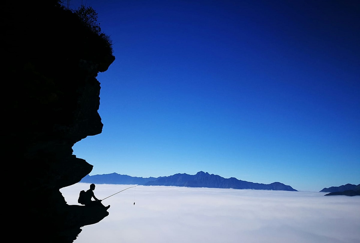 Waves of clouds at the bottom of a cave on the way to Lao Than peak. In the picture, a tourist holding a fishing rod to pose for a photo that might give impression that he is fishing. Photo by Sung A Tru.