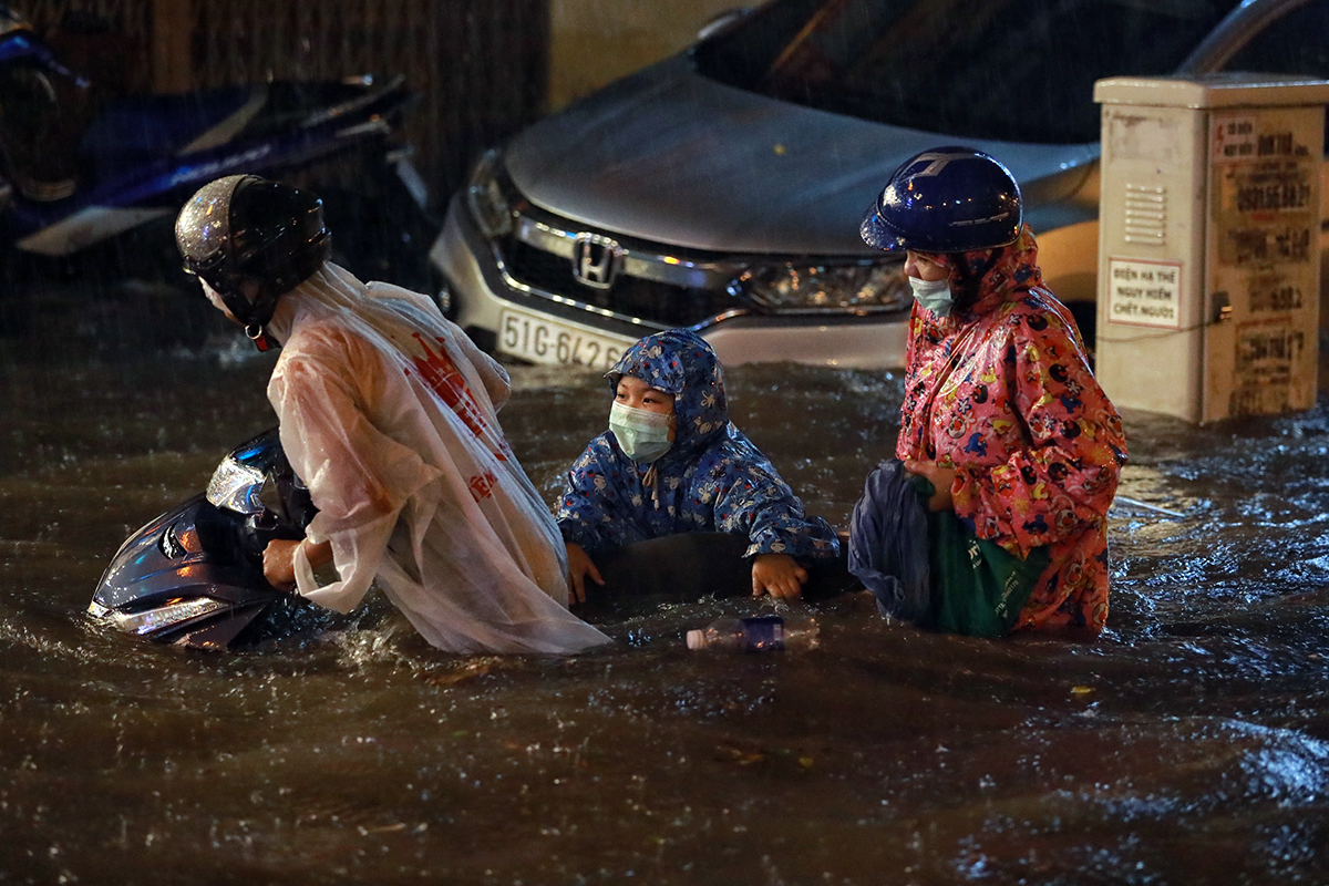 A family struggles to wade through a flood water on Nguyen Huu Canh Street after a heavy rain has just stopped on the night of August 6, 2020. Photo by VnExpress/Huu Khoa