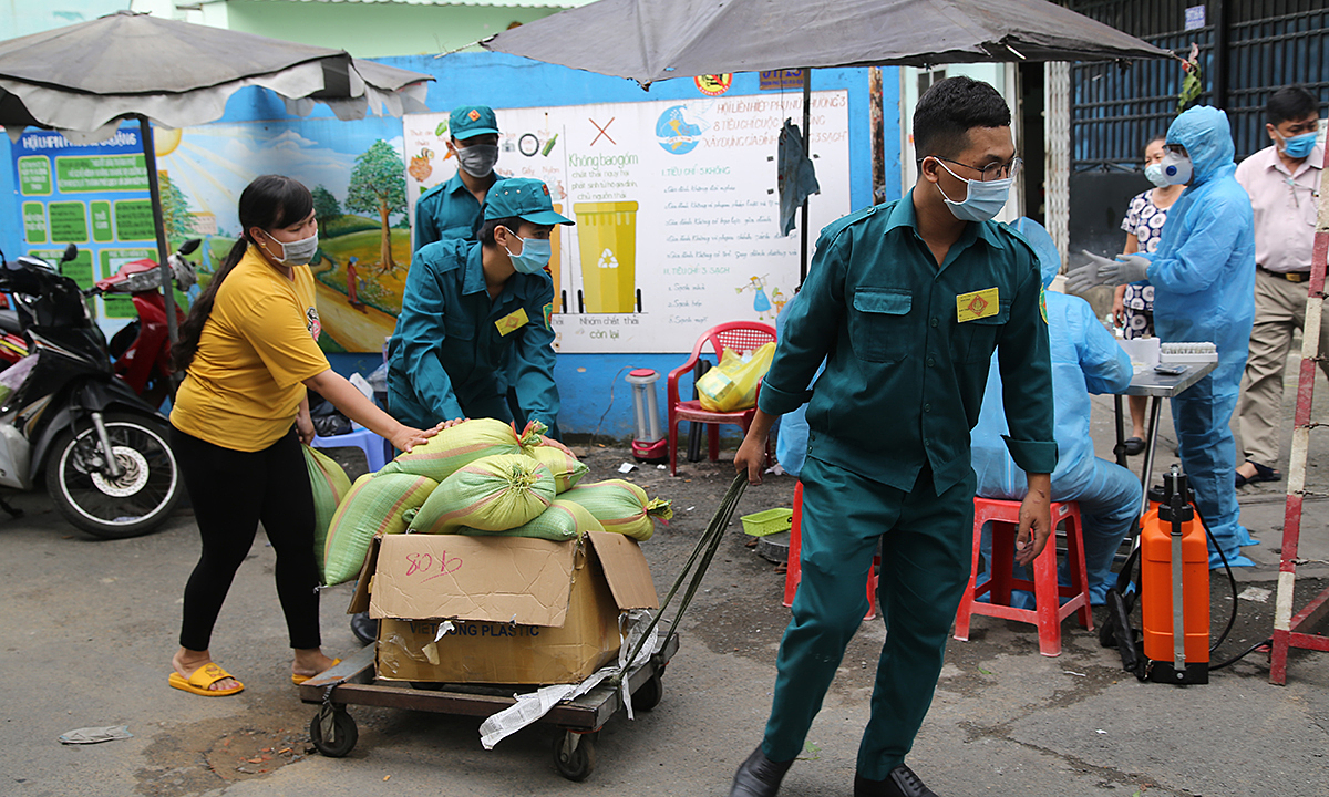 Civil defense personnel bring rice aided by local authorities to an isolated neighborhood in HCMCs District 6 after a man living there was confirmed a Covid-19 patient, December 1, 2020. Photo by VnExpress/Dinh Van.
